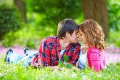 Bella giovane coppia innamorata sdraiato nell'erba di primavera — Foto Stock