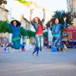 Three happy girls jumping on crowded city street — Stock Photo