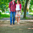 Young pregnant couple walking spring park — Stock Photo