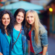 Three beautiful girls on evening street — Stock Photo