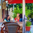 Beautiful girls sitting on cafe terrace, summer city — ストック写真