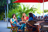 Young female friends sitting on cafe terrace, urban outdoors — Stock Photo