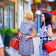 Two beautiful women walking the city street — Stock Photo