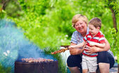 Happy grandmother with grandchild roasting meat on picnic — Stock Photo