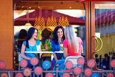 Happy girls sitting on summer cafe terrace — Stock Photo