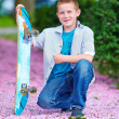Teenage boy with skateboard in spring garden — Stock Photo #26107655