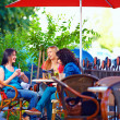 Beautiful young women sitting on cafe terrace — Stock Photo #26222367