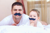Funny father and son with false mustaches, playing at home — Zdjęcie stockowe