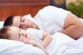 Father and baby sleeping peacefully in bed — Stock Photo