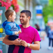 Candid image of father and son walking crowded street — Stock Photo #26507449