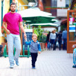 Stock Photo: Candid image of father and son walking street
