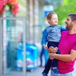 Happy father and son walking city street — Stock Photo #26507495
