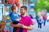Candid image of father and son walking crowded street — Стоковое фото