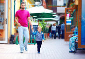 Candid image of father and son walking the street — Stock Photo