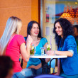 Three beautiful girls sitting on cafe terrace — Stock Photo #26610961