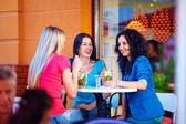 Three beautiful girls sitting on cafe terrace — Stock Photo
