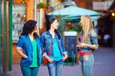Happy female friends on evening street — Stock Photo