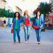Three young girls walking the city street — Stock Photo