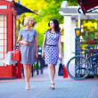 Beautiful women walking the city street with shopping bags — Stock Photo