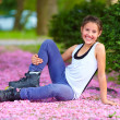 Cute girl roller-skater in spring park — Stock Photo