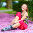 Cute girl roller-skater in spring park — Stock Photo #26899837