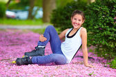 Roztomilá dívka roller-skater v parku na jaře — Stock fotografie