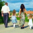 Family together walking the footpath, village background — Stock Photo