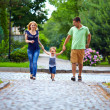 Stock Photo: Happy family of three persons running the street