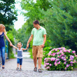 Stock Photo: Happy family of three persons walking the street