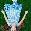 Beautiful happy girl kid lying on green grass — Stock Photo
