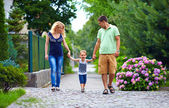 Happy family of three persons walking the street — Foto Stock