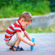 Stock Photo: Small kid painting the ground with chalk