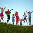 Happy kids jumping on summer field — Stock Photo #27909627
