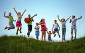 Happy kids jumping on summer field — Stock Photo