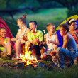 Stock Photo: Group of happy kids roasting marshmallows on campfire