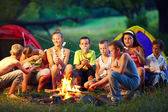 Group of happy kids roasting marshmallows on campfire — Stock Photo