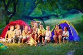 Group of happy kids roasting marshmallows on campfire — Stock Photo
