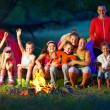 Happy kids having fun around camp fire — Stockfoto