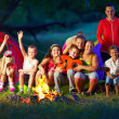 Happy kids having fun around camp fire — Stock Photo
