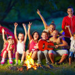 Happy kids singing songs around camp fire — Stock Photo