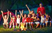 Glückliche kinder singen lieder rund um lagerfeuer — Stockfoto