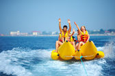 Happy people having fun on banana boat — Stock Photo