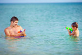 Happy father and son playing with water pistols — Stok fotoğraf