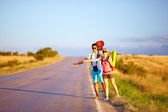 Young people traveling hitchhiking. summer road — Stock Photo