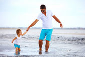 Father and son overcome obstacles together, salted firth — Stock Photo