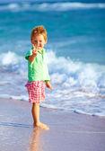 可爱的男孩在海滩上显示胜利手势 — 图库照片