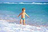 милый ребенок мальчик, с удовольствием в морской прибой — Стоковое фото