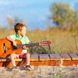 Portrait of cute boy playing a guitar on summer field — Stock Photo