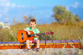 Cute boy playing a guitar on summer field — Stock Photo