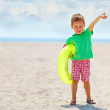 Happy kid with rubber ring on summer beach — Stock Photo